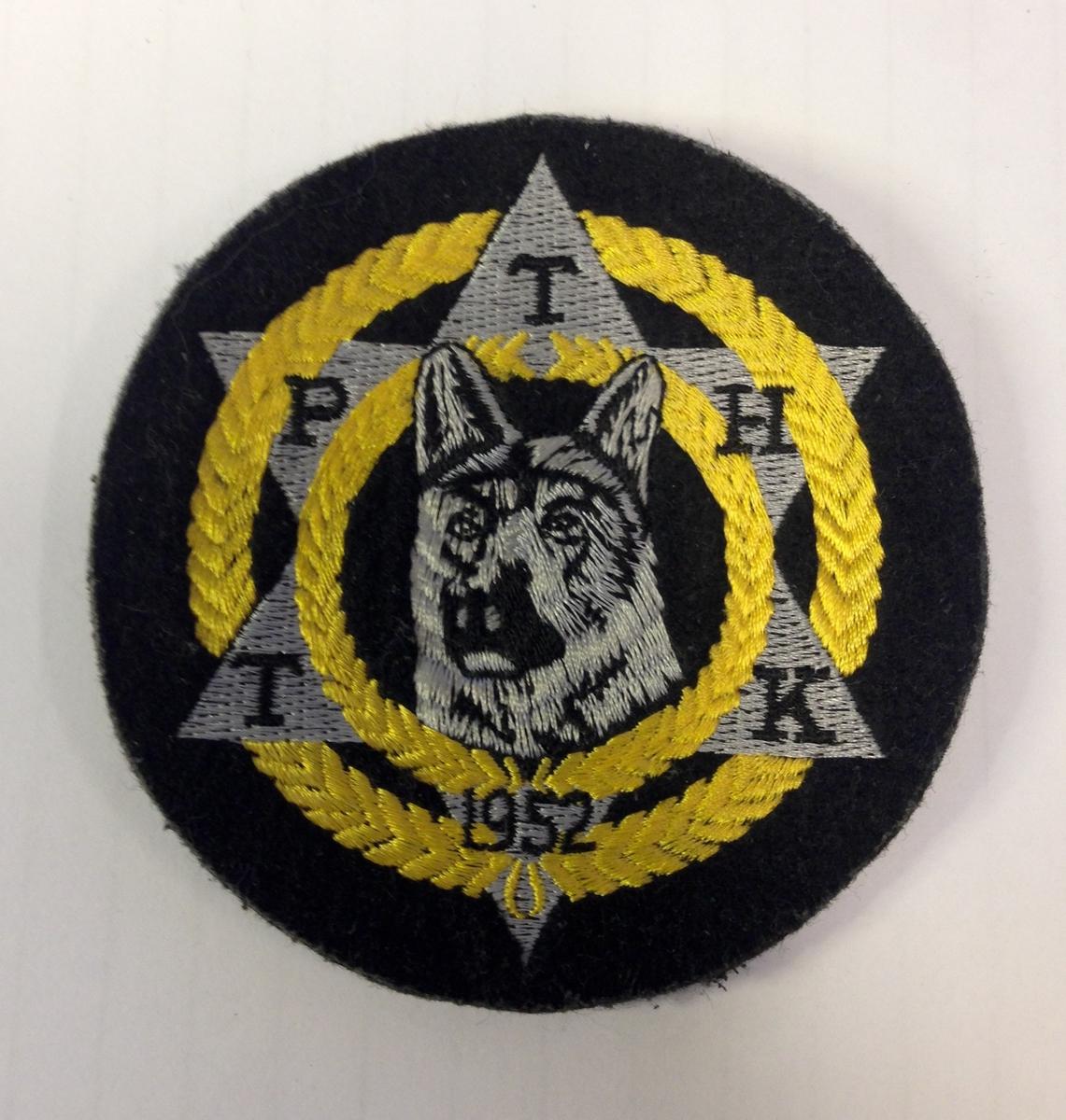 Rundt merke i stoff med maskinbrodert logo i hvitt, sort og gult.
