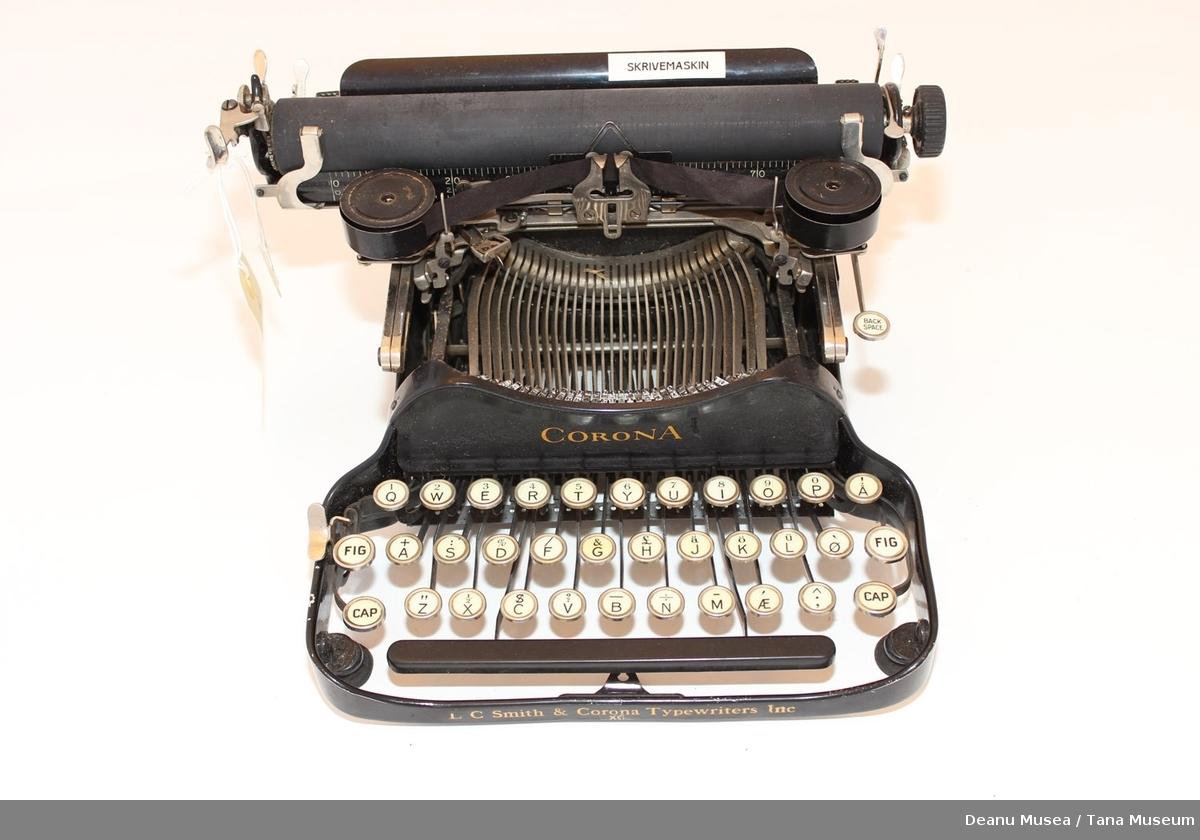 Skrivemaskin i sort og blank metall med påskrift i gull.