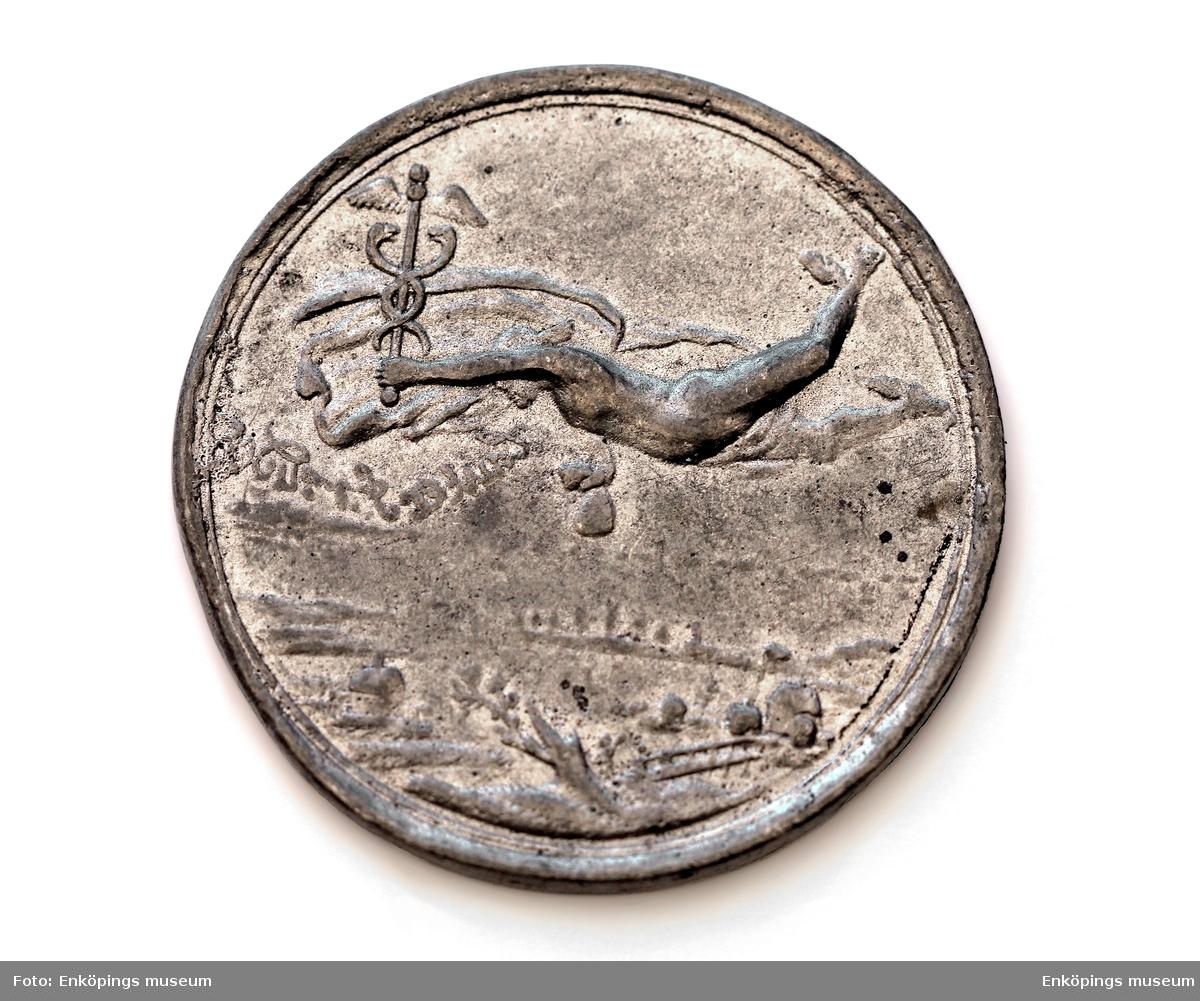 Rund medalj gjuten i tenn. På framsidan bild av en flygande Hermes ihållande en bevingad stav omslingrad av två ormar. På baksidan två palmkvistar med tysk text runt om. I mitten en fyrkant med en triangel inuti. Årtalet 1689 i romerska siffror.   Avgjutningar av medaljer i Grönsösamlingar.