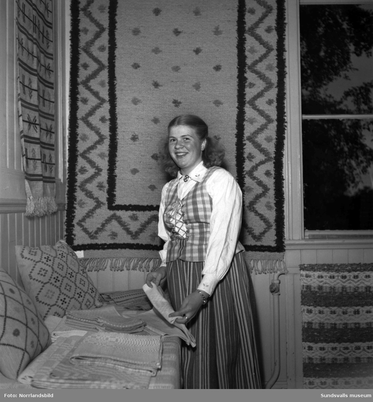 Avslutning för Alnö yrkesskolor. En flicka i folkdräkt visar upp olika textilarbeten.