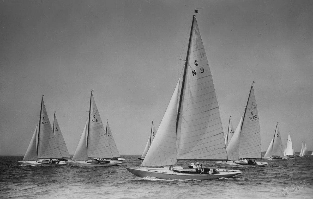 Fartyg:  Bredd över allt 2,05 meter Längd över allt 10,15 meter  Konstruktör: Aas, Bjarne Övrigt: Fotografiet återgivet i Lybeck (red.): Nordens Båtar vol. I (Sthlm 1939) s 244. Enligt baksidesanteckningarna ska bilden även ha återgivits i Till Rors. Enligt bildtexten i Nordens Båtar visar detta fotografi IOD-båtar vid Hankö-regattan; tidpunkt oviss. Segelnummer fr v t h N21, N6 (skymd), N8, N11 (skymd), N3 (skymd), N9 (närmast kameran), N18 (skymd), N22 (skymd) och N2 (skymd).