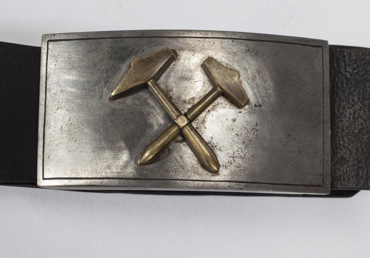 Lærbelte med jernspenne. På spenna bergmannssymbolet korslagt hammer og bergsjern i messing. Oval metallplate med fire hull og inskripsjon naglet fast til beltet.