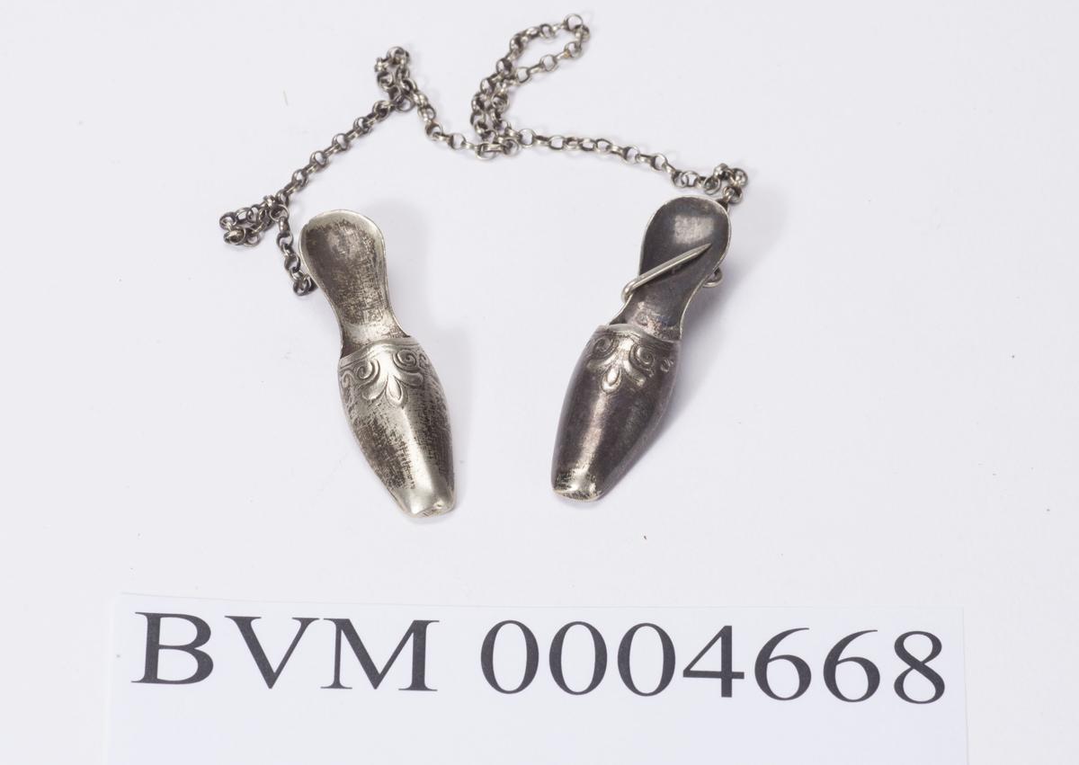 """Hekte av sølv med kjede. Kjede ca. 26 cm langt. To """"anheng"""" formet som sko."""