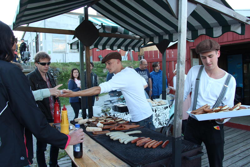 To personer griller og selger grillmat til besøkende.