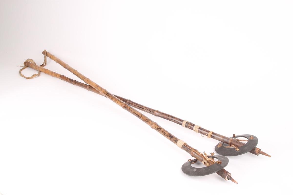 Et par bambusstaver med håndtaksremmer i bomull, samt mørke horn(?)-trinser. Trinsen er festet til staven med en lærrem, som går gjennom et hull i staven. Nederst på staven er det festet en holk og stavpigg i jern. Det er surret tråd rundt den nederste delen av stavene, trolig i forbindelse med en reparasjon da begge stavene er sprukket.
