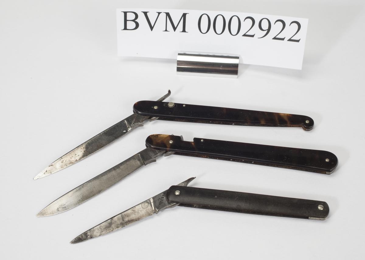 Tre kirurgiske foldekniver av samme type. To med låsemekanisme, hvorav den ene er defekt. Den tredje kniven er uten låsemekanisme.