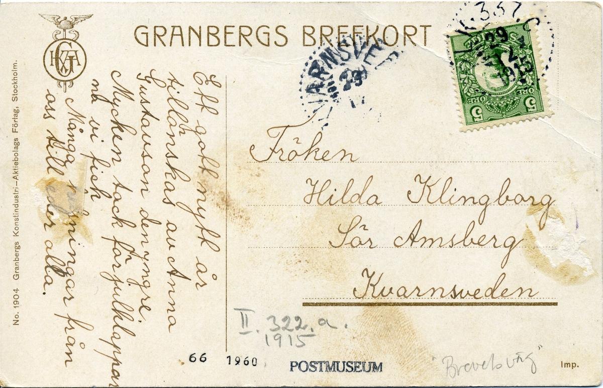 """Nyårskort med motiv av kvinna som lägger ett brev på en röd brevlåda. Brevlådan är upphängd på ett staket med affischer om """"nyårsvaka"""", """"vid årsskiftet"""" och """"gott nytt år"""". Adressidan visar att kortet är avsänt från med postkupé till Kvarnsveden 1915."""