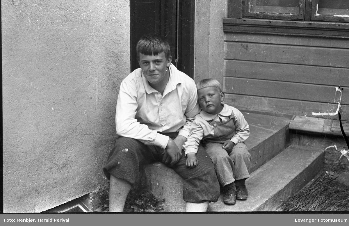 Per Renbjør og en liten gutt på trappa ved Renbjørs foto- og musikkforretningen.