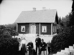 Envånings parstuga, familjegrupp 5 personer framför stugan.