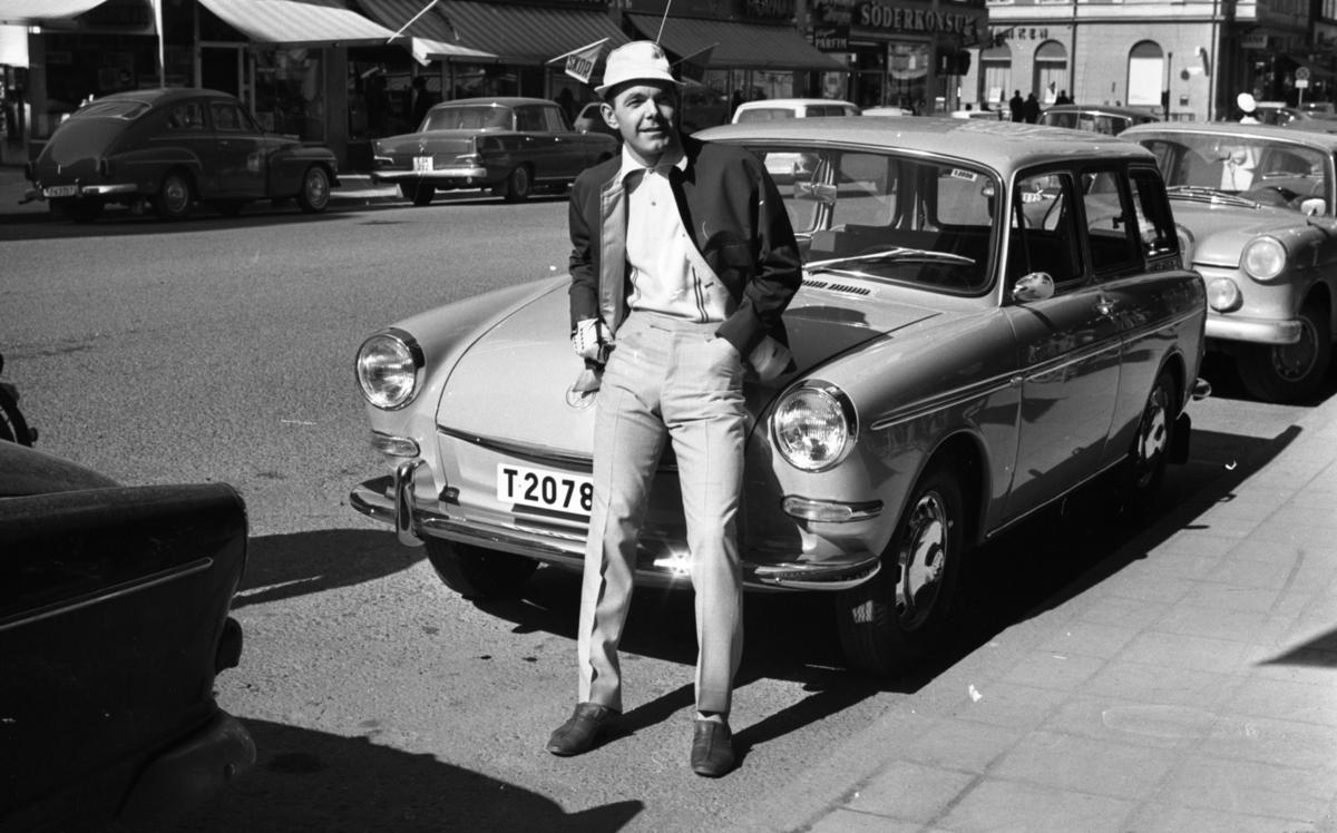 Andersson Gustavsson mode 23 april 1966En manlig fotomodell visar herrkläder. Han är iklädd jacka, tröja. byxor, skor, handskar och hatt. Han lutar sig mot motorhuven på en parkerad bil. I bakgrunden syns flera bilar samt personer och hus.
