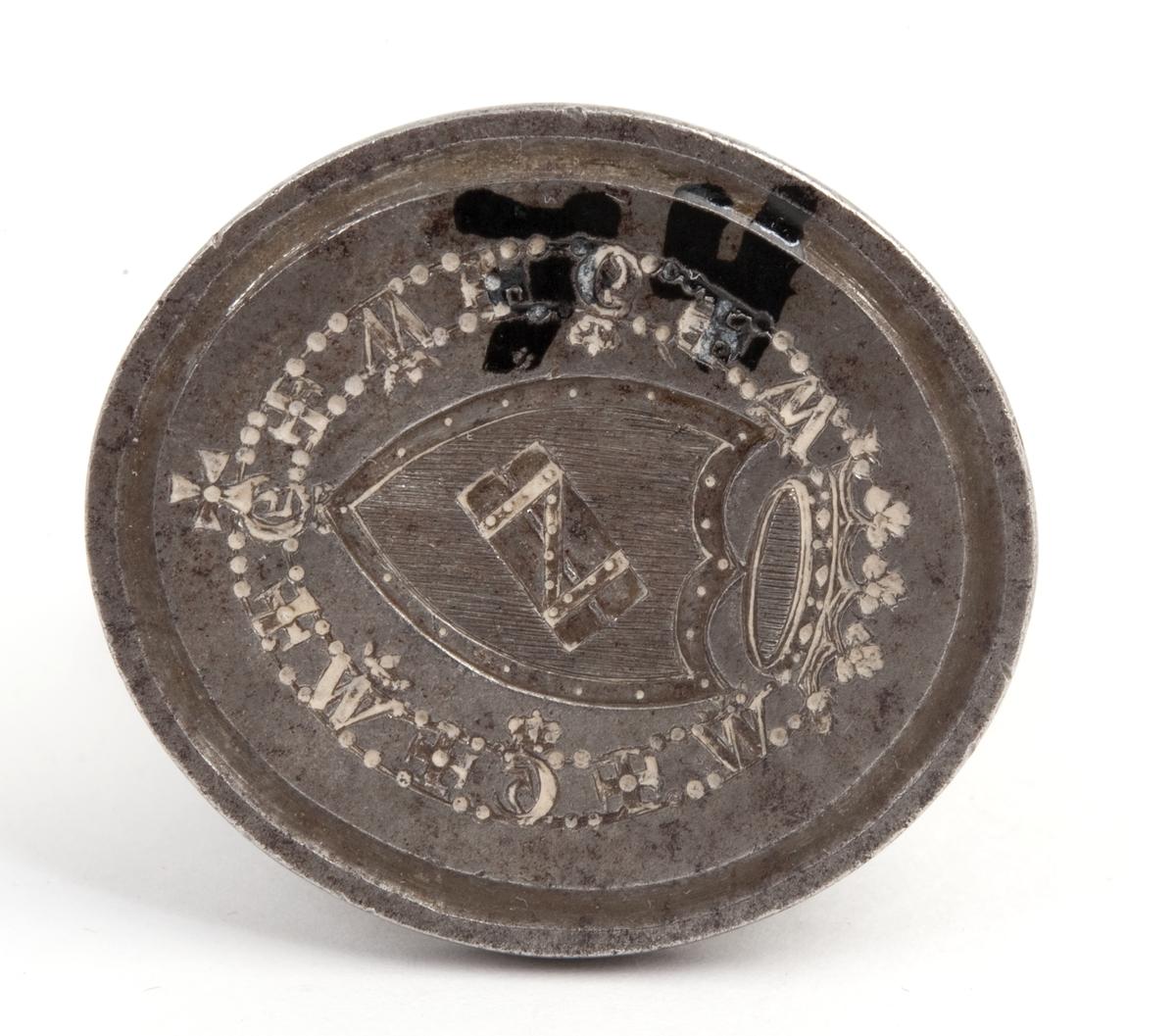 Stempelet har form som et skjold. Krone øverst, bord med bokstaver rundt, ovalt håndtak med enkel utsmykning. Efter General Haxthausen.