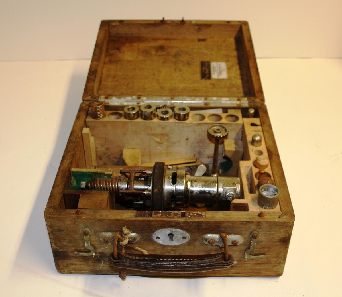 Gjenstanden består av en trekasse med instrument og flere instrumentdeler i; blant annet en oljeflaske, metallfjærer, og fire linjaler. Trekassen har to klemmelåser samt lås med nøkkel. Håndtaket er av skinn, festet til kassen med metall. Lokket er hengslet på.