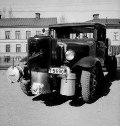 Lastbil med gasgenerator frammonterad.Bostadshus i bakgrund