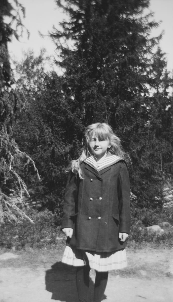 En jente med flagrende hår står på en skogsvei.