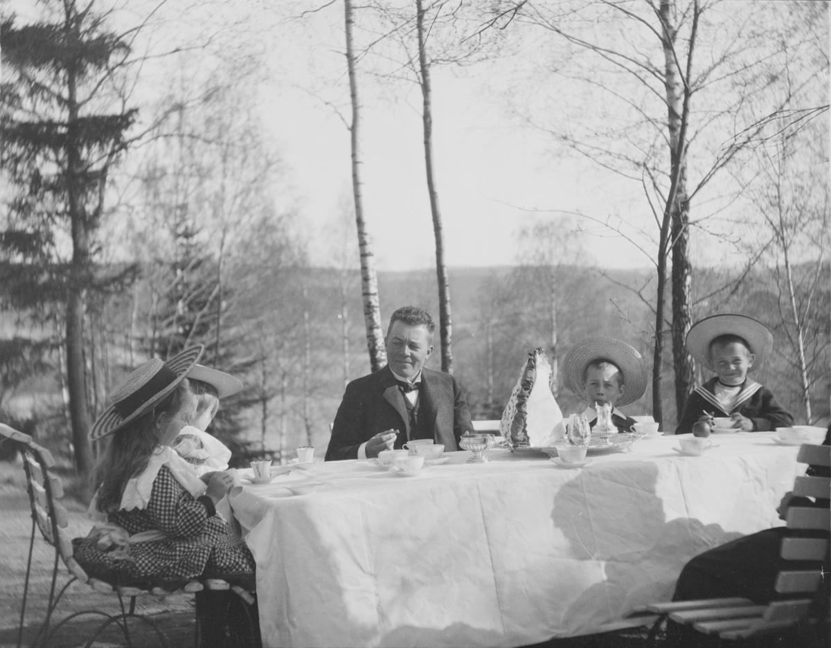 Statsråd Christian Pierre Mathiesen med Christian Pierre f. 1897 og Erich Monsen til høyre i bildet, og Ise (Louise) og Iacob til venstre i bildet ved et bord med hvit duk med oppdekking til kaffe og/eller teselskap i hagen. Vi ser en bit av en voksen person til, sannsynligvis en kvinne.