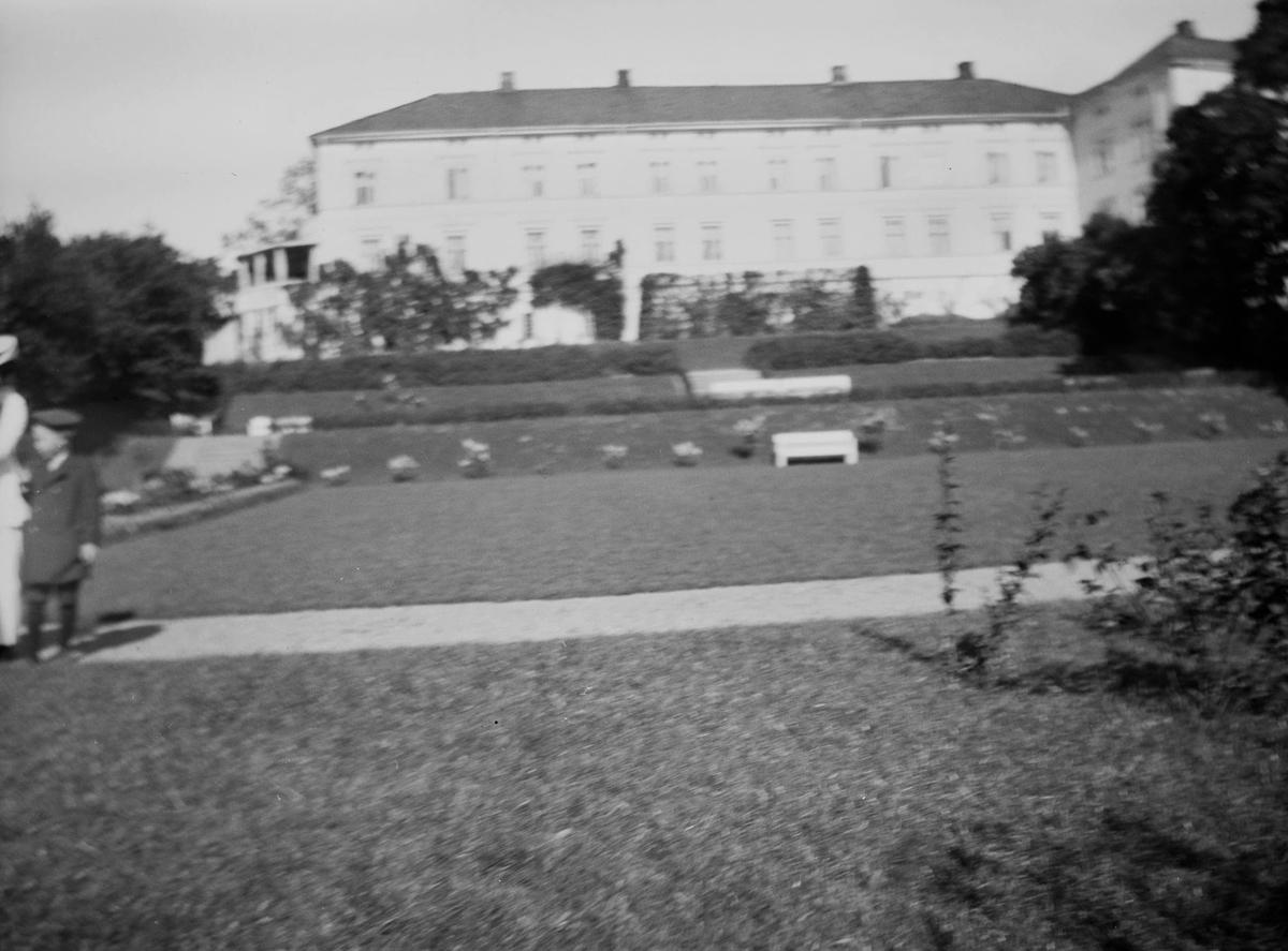 Linderud Gård med hage, er ute av fokus. Det er sommer og i billedkanten sees en gutt og en kvinne i fine sommerklær.