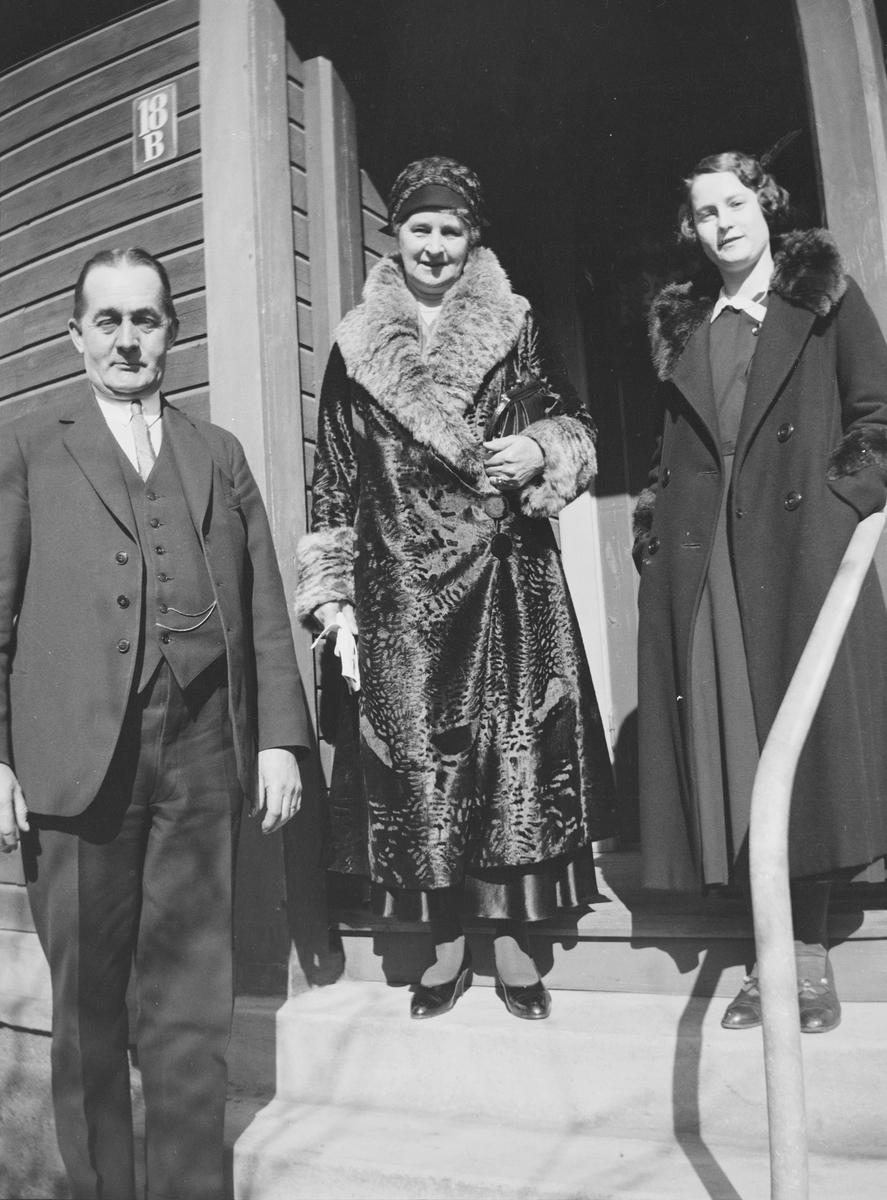 En mann og to kvinner står på trappen til et trehus. Solen skinner, det sen vinter eller tidlig vår. Alle tre ser på fotografen. Kvinnene er kledd i varme kåper. På husveggen er det et skilt med husets nr; 18 B.