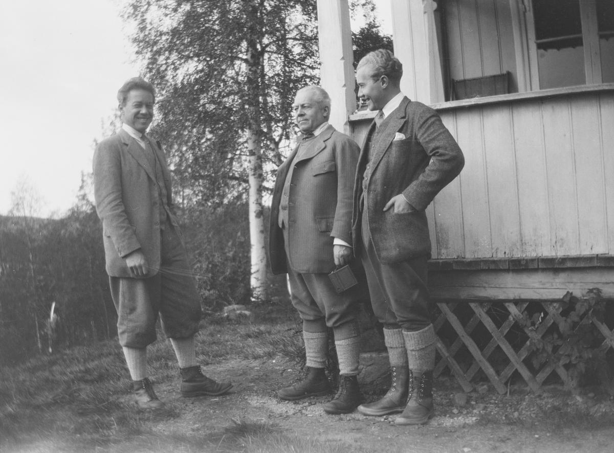 Tre menn; Christian Pierre samt sønnene Haaken og Iacob, står sammen utenfor inngangspartiet til familiens hus i Jeppedalen. Alle smiler og ser fornøyde ut. Bildet er tatt i sommerhalvåret.