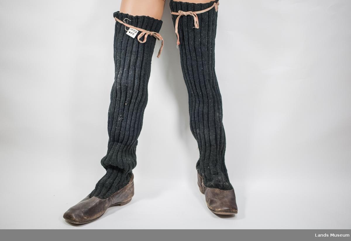 Sko i lær med påsydde strikkede strømper i ull. Hæl festet med spiker. Grindvevde bånd i rødt, kvit og svart for feste øverst.