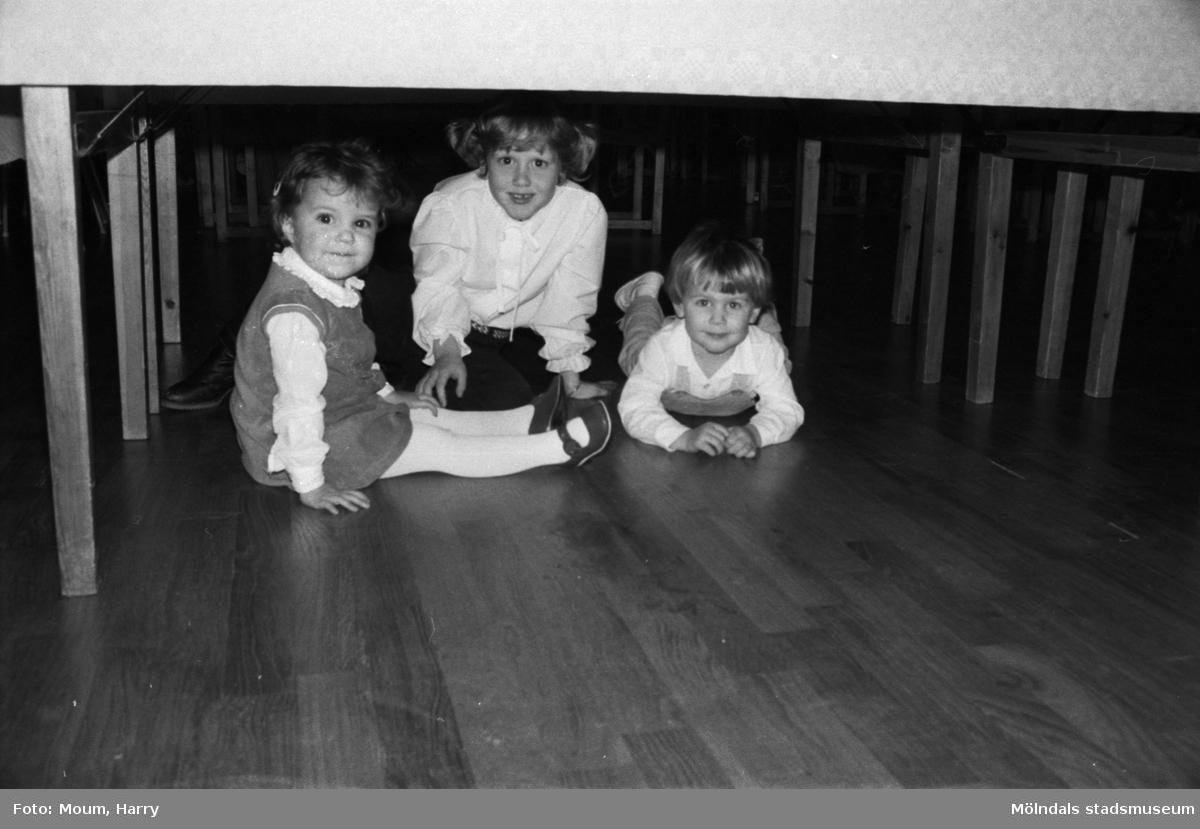 Lindome hembygdsgilles julgille på Hällesåkersgården i Lindome, år 1984. Tre barn under ett bord.  För mer information om bilden se under tilläggsinformation.