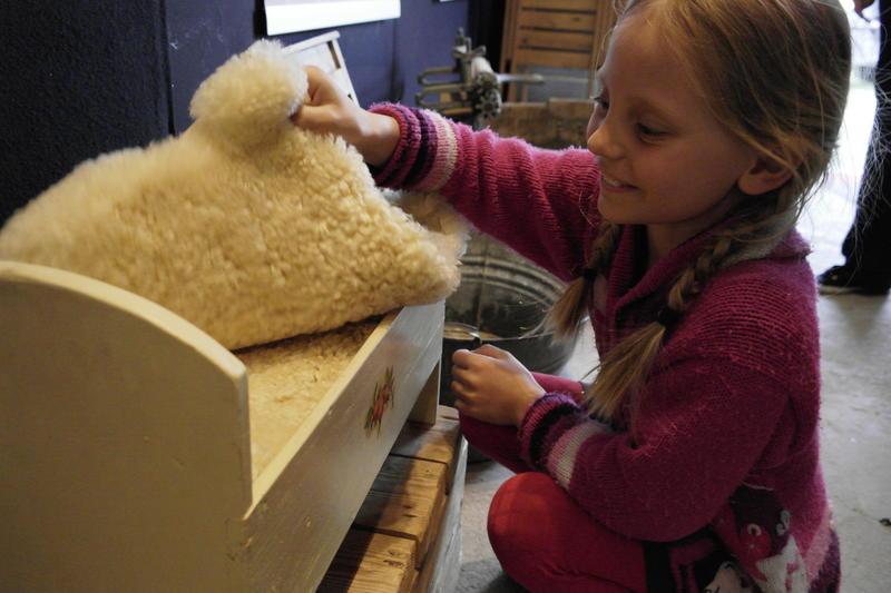 Jente som kikker i en dukkeseng med skinnfell og halmmadrass.