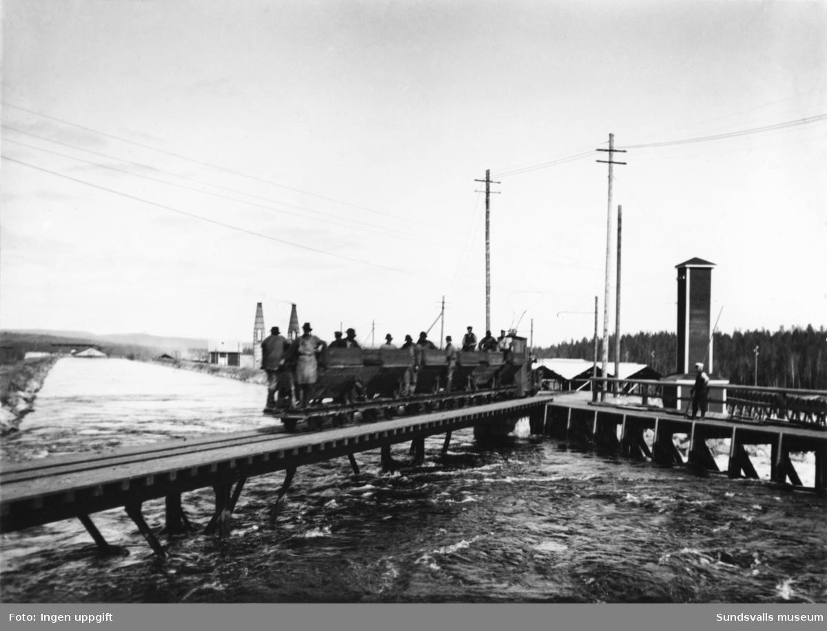 Alby kraftstation. Bro över kanalen vid intaget. Kolvagnar på räls över bron. Mannen med båtshaken är nattvakten Boström. I bakgrunden ses Alby karbidfabrik.