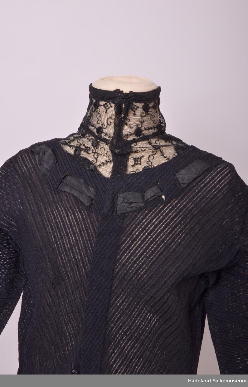 Svart. Ull og bomull, mønstervevd i striper. Ponchosnitt. Høy hals med spiler. Stoff og snitt som HF 5531. Annet broderimønster på tyllinnfelling i halsen. Ikke tyll nederst på ermene. Knapphullsting på erme, ikke rysj øverst på halsen. Båndfeste nedenfor nederste trykknapp