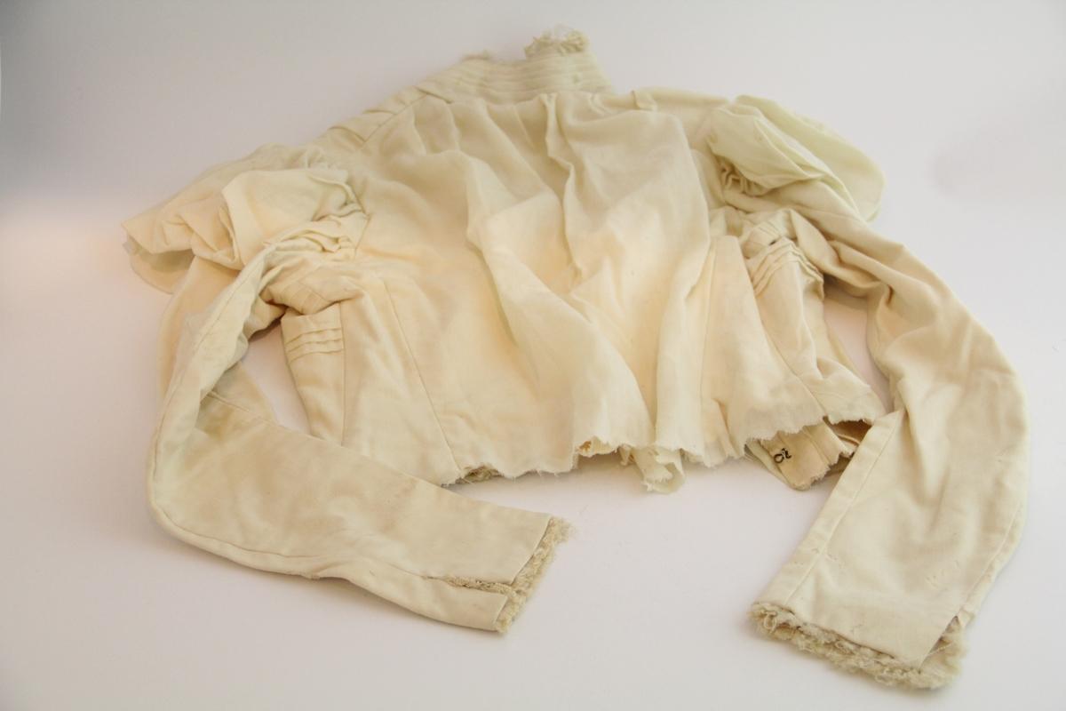 Trøye/kjoleliv i hvitt bomullsstoff. Høy krage. Kneppes ved hemper. Puffermer. Påsydd tylllignende stoff i ermene og i kragen. Tversgående folder langs forstykke. Ikke avsluttet ved livet, foldet og innsydd.