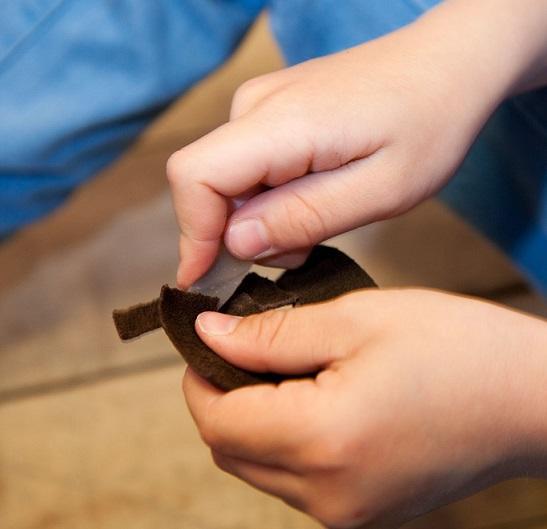 Nærbilde av barnehender som skjærer i en skinnbit med en steinflekke (Foto/Photo)