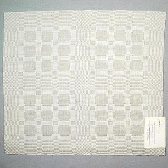 """Tablett vävd i jämtlandsdräll. Grått dubbelspolat lingarn i inslag, blekt bomullsgarn i varp. Märkt med tryckt pappersetikett från Jämtslöjd med handskriven text i bläck: """"Jämtlandsdräll  Gammalt mönster  Maria Moden Olsson"""". Etiketten har också en stämplad text: """"Länshemslöjdskonsulenten  Heimbygdas slöjdnämnd  Länsmuseet  831 00 Östersund""""."""