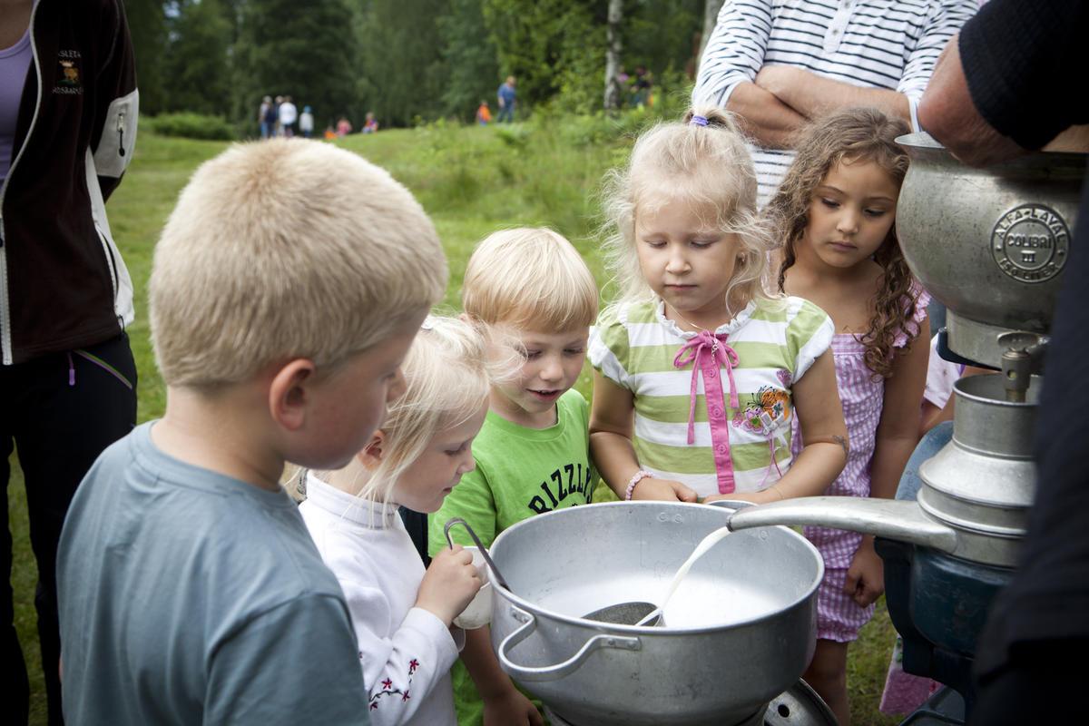 Flere barn som står rundt et melkeseparator og ser på hvordan melk separeres