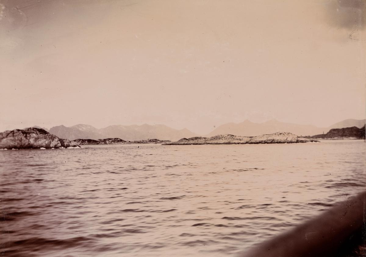 Holmer og skjær, i bakgrunnen - fjell.