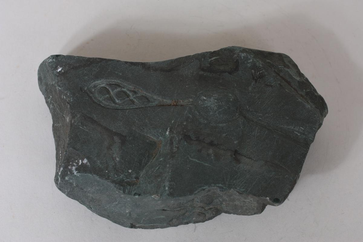 Forholdsvis stor og tung stein som er knudrete på eine sida og glattare på støypesida.
