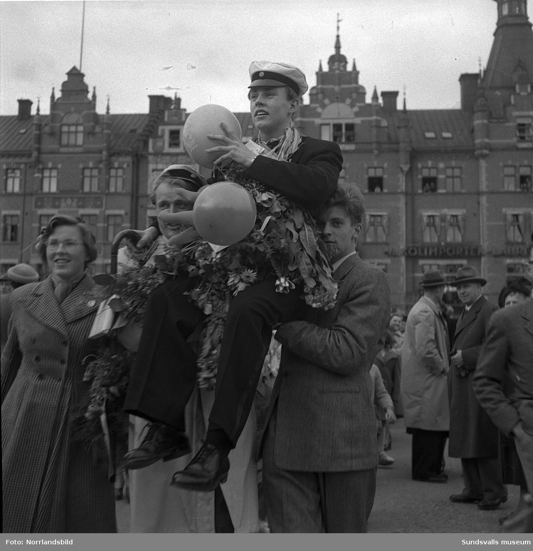 Studentexamen 1951. Studenterna på läroverkets trappa och tågandes utefter Köpmangatan mot stora torget.
