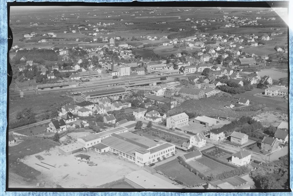 Bryne med jernbanestasjonen i midten.Mellom her og  industribygget i framgrunnen til Erland Maskin AS ligg Brødr. Hetland sitt industriområde.