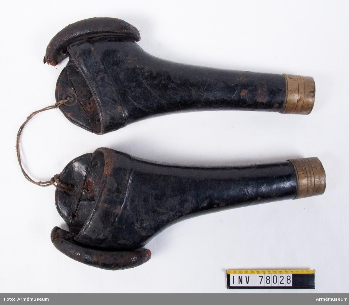 Grupp K I. Pistolhölster till sadelmundering för officershäst; 1845.  Sadelmunderingen består av: 1 sadel med tillbehör 2 förbygel 3 ryggstycke 4 valltrapp m/1876 5 övergjord 6 omslagsrem 7 stång- och bridongbetsel 8 pistolhölster, 1 par 9 hästmannekäng (Inköpt 1914)  Betslet utgöres av: 1) bridong, 2) stångbetslet och 3) halsgrimma med grimskaft.  Bridongen består av: 1) huvudlag, 2) bridongbett och 3) bridongtyglar.  Huvudlaget  består av: a) nackstycke, 15 mm bred, b) sidstycken, 15 mm breda, varje med två svartlackerade söljor. Bridongbettet påminner om m/1867, men har tvådelat bett och består av: a) tvådelat bett, med 14 cm bredd mellan tygelringarna, b) tygelringar, 50 mm i diam, med uppstående sidstänger, vilka utformade upptill till ringar, 30 mm i diam, för att sammankopplas med sidstyckena.  Bridongtyglarna är 16 mm breda, hopspända i tygelringarna och med varandra.  Stångbetslet består av: 1) huvudlag, 2) stångbett och 3) stångtyglar.  Huvudlaget består av: a) nackstycke, 30 mm brett, med dubbla stroppar, en kedja av järn, 15 cm lång, två hakar och ett hakeläder med hake, b) sidstycken, 15 mm breda, varje med två svartlackerade söljor, c) käkrem, 15 mm bredl ned två svartlackerade söljor, d) pannrem, 23 mm bred, rörlig, e) nosrem, 15 mm bred, trädd genom sidstyckena och försedd med en svartlackerad sölja. Stångbettet påminner om m/Sandström och består av: a) mellanstycke, med 12 cm bredd mellan sidstängerna och kraftig uppbockning, b) sidstänger, fasta och raka, 16,5 cm långa, c) vridbara tygelringar, 33 mm i diam, d) lös kindkedja.  Anm m/Sandström, se Tygmaterielkatalog KAFT nov 1947. Stångtyglarna är 17 mm breda, hopspända i tygelringarna, sammansydda med varandra och försedda med en löpare.  Halsgrimma med grimskaft. Halsgrimma består av: a) halsrem, 20 mm bred, som spännes med en sölja på sidan om hästens hals, b) ringläder med fastsydd järnring, för att sammankopplas med stångbetslet, c) mitt under hästens hals finns en fastsydd järnring för grimska