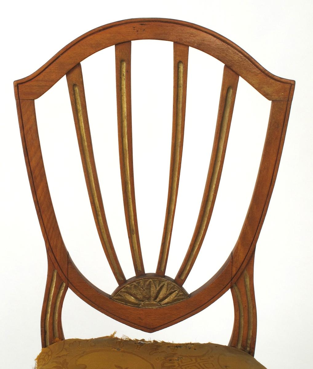 """Stol. Beiset og polert bøk.  Setet stoppet på striebånd og trukket med gul ulldamask (utslitt). Rygg ekte Hepplewhite, åpen, skjoldformet,  med """"skuldre"""", med 4 smale spiler som strekker seg opp av utskåren halvmåneformet rosett nederst i skjoldspissen. Smal sarg, rette ben, kvadratiske, avsmalnende, med liten tverrgående kil ved sargen. H-formet bindeledd mellom benene."""