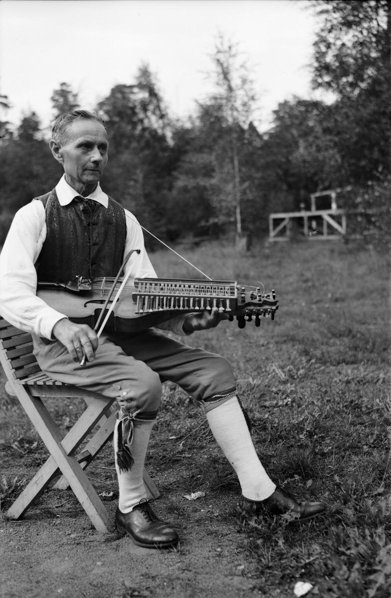Spelmannen August Bohlin med nyckelharpa vid spelmanstävling i Granebergsparken, Sunnersta, Uppsala augusti 1945