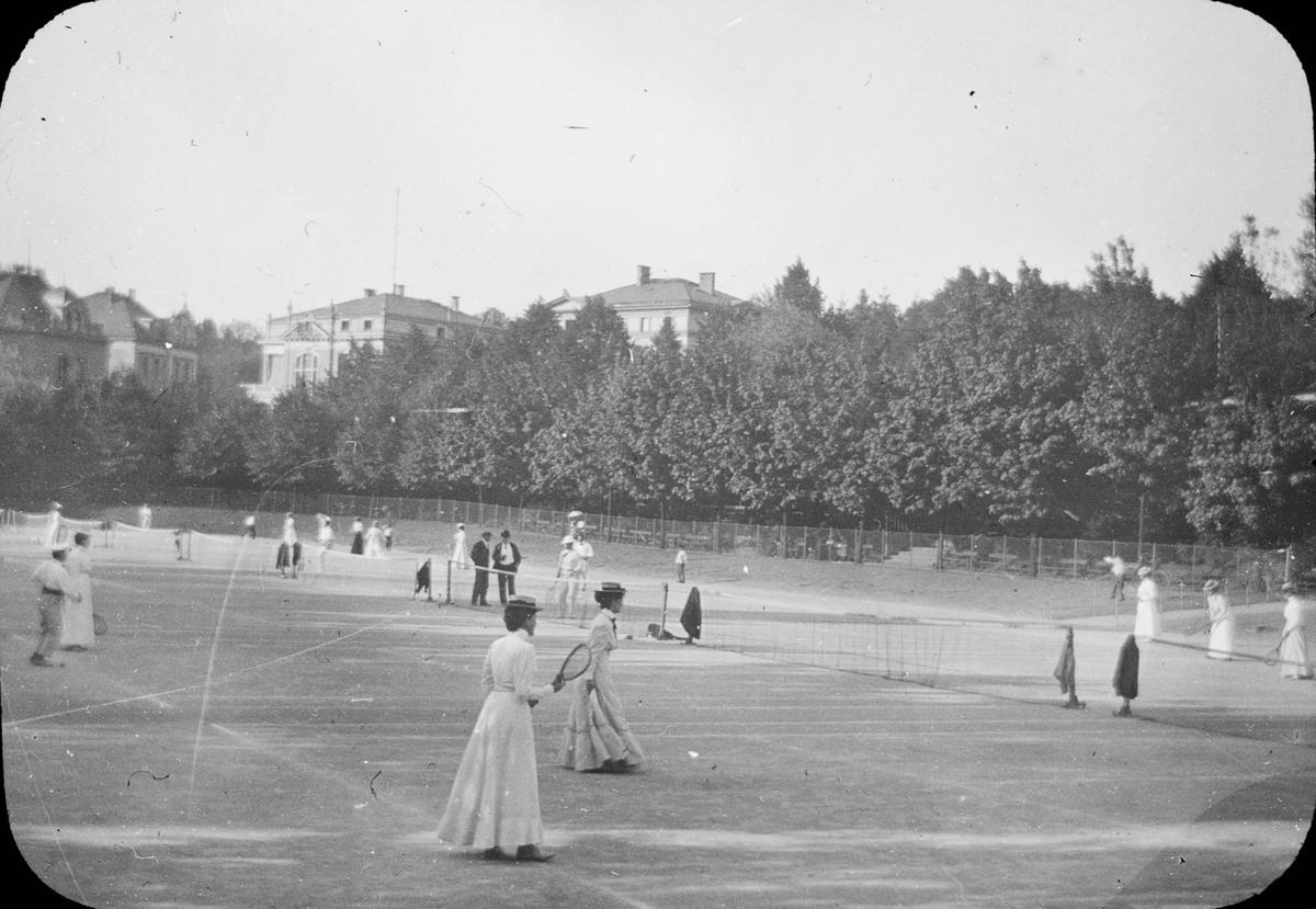 """Skioptikonbild med motiv av tennissspelare i Wiesbaden. Bilden har förvarats i kartong märkt: Wiesbaden. Rhen. Text på bild: """"Laura Tennis""""."""