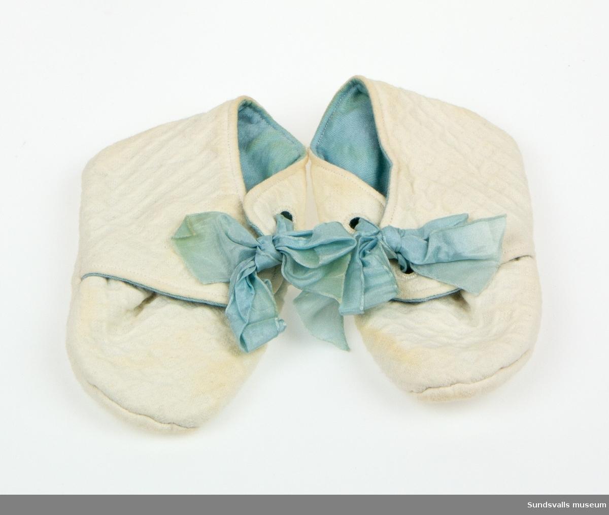 Et par tyg-skor i vit våfflat bomullsstyg med blått foder och blå sidenband.