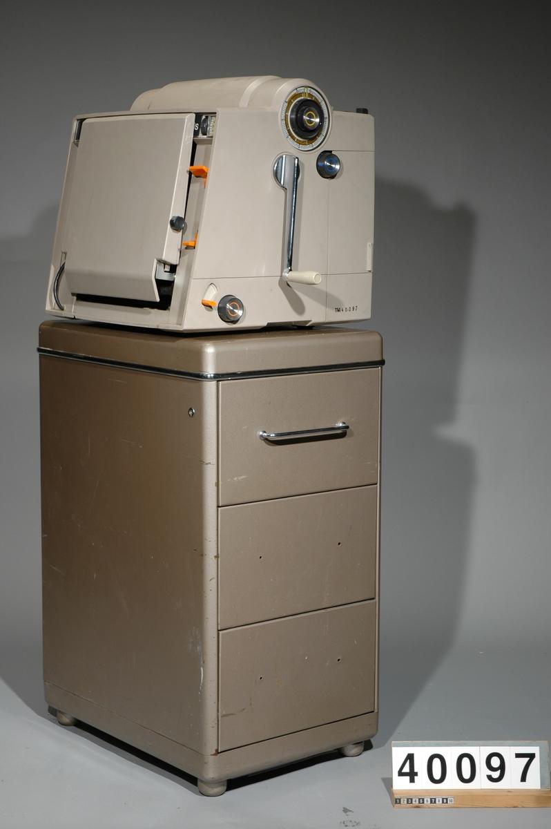 """Stencilapparat, Gestetner 460s, 200W. 46kg. L 425mm B 490 H 450 Skåp av metall för div. tillbehör med tre lådor, Mått: 410bx590lx800h, vikt inkl innehåll: 54 kg. Innehåll: 7 st paket stenciler, 17 st tuber grå färg och rengöringsvätskor 1st instuktionsbok för Stencilerings apparat Gestetner 466. Ca 150st påbörjade stenciler m text """"Tonårsbrevet"""" Skåp av plywood vari man förvarade färdiga och infärgade stenciler, grått, tomt. 8kg Bredd: 570 mm, längd: 175 mm, höjd: 573 mm. Brännare, Gestetner 473, No F92426, 200W, tysk, ljusbrun plast. vikt 23kg Bredd: 390 mm, längd: 690 mm, höjd: 225 mm."""