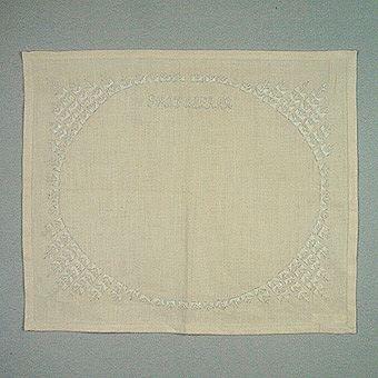 """Tablett broderad i Hallandssöm. Broderad på halvblekt halvlinne med vitt bomullsgarn. Mönstret består av en broderad ram i flätstygn och texten """"GRATULERAR"""" i stjälkstygn."""