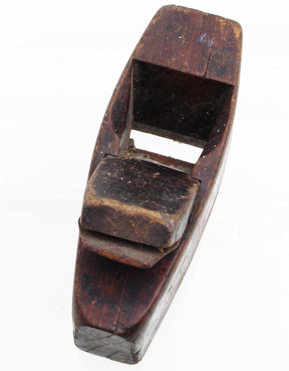 Høvel. Bøk, brunbeiset. Avsmalnende bakover, på oversiden foran innskåret bokstav. Jern og plugg.