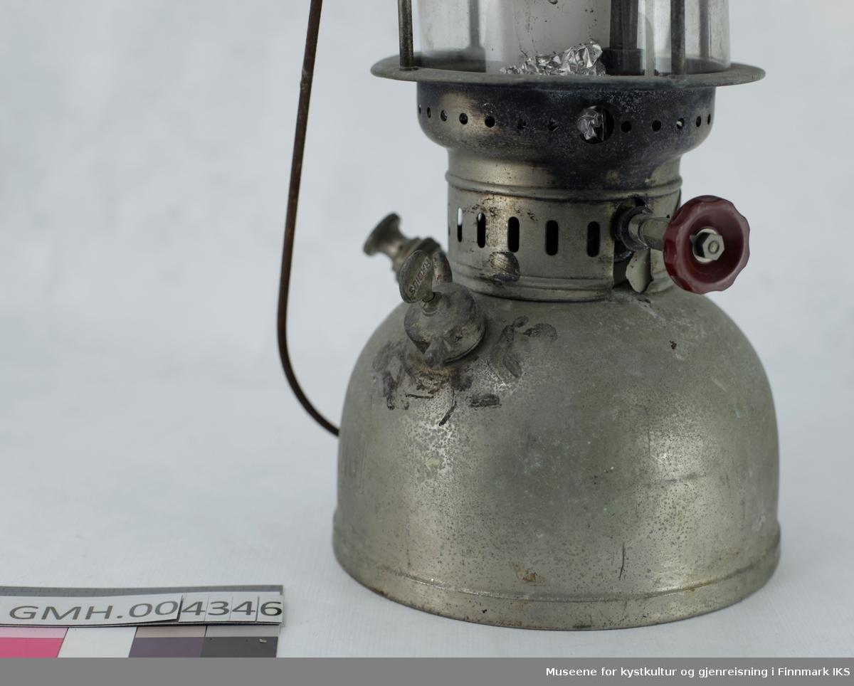 Lampen har en drivstoffbeholder med fyllåpning med skrulokk og en pumpe. Den brukes til å skape trykk i beholderen som så presser drivstoffet gjennom forgasseren slik at den fordampes og forbrennes i en glødestrømpe.  I tillegg befinner det seg et hjul på motsatt side som regulerer strømingsmengden av drivstoffet. Der lyset oppstår er det satt inn et sylindrisk glass. Dette kan ved behov skiftes ved å løse de to skruene som holder håndtaket. Slik kan den øvre delen av lampen løftes av. Lyktet ble brukt med et kubbelys som dekorasjon som står på aluminiumsfolie. Ved overdragelsen av gjenstanden var drivstofftanken fylt med en veske. Den ble fjernet pga. brannfare. Den øvre delen av lyktet er deformert ved en av de festeskruene og kan derfor ikke festes på denne siden. Gjenstanden er sammensatt av deler fra forskjellige produsenter. Drivstofftanken viser HASAG sin merke mens forgasseren er merket Petromax som viser til Ehrich & Graetz.