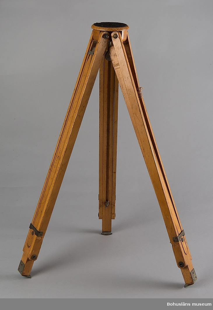 Kamerastativ av trä med tre ben.  Föremålet ingår i fotograf Ingeborg Enanders ateljéutrustning i fotoateljén i Stenungsund. För ytterligare uppgifter om förvärvet, se UM71.22.1.