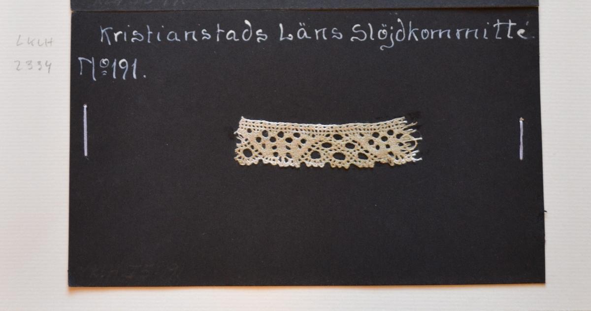 Kristianstads Läns Hemslöjdskommitté No 191. Sexhålstagg med tulpan. Provet är monterat på svart kartong.