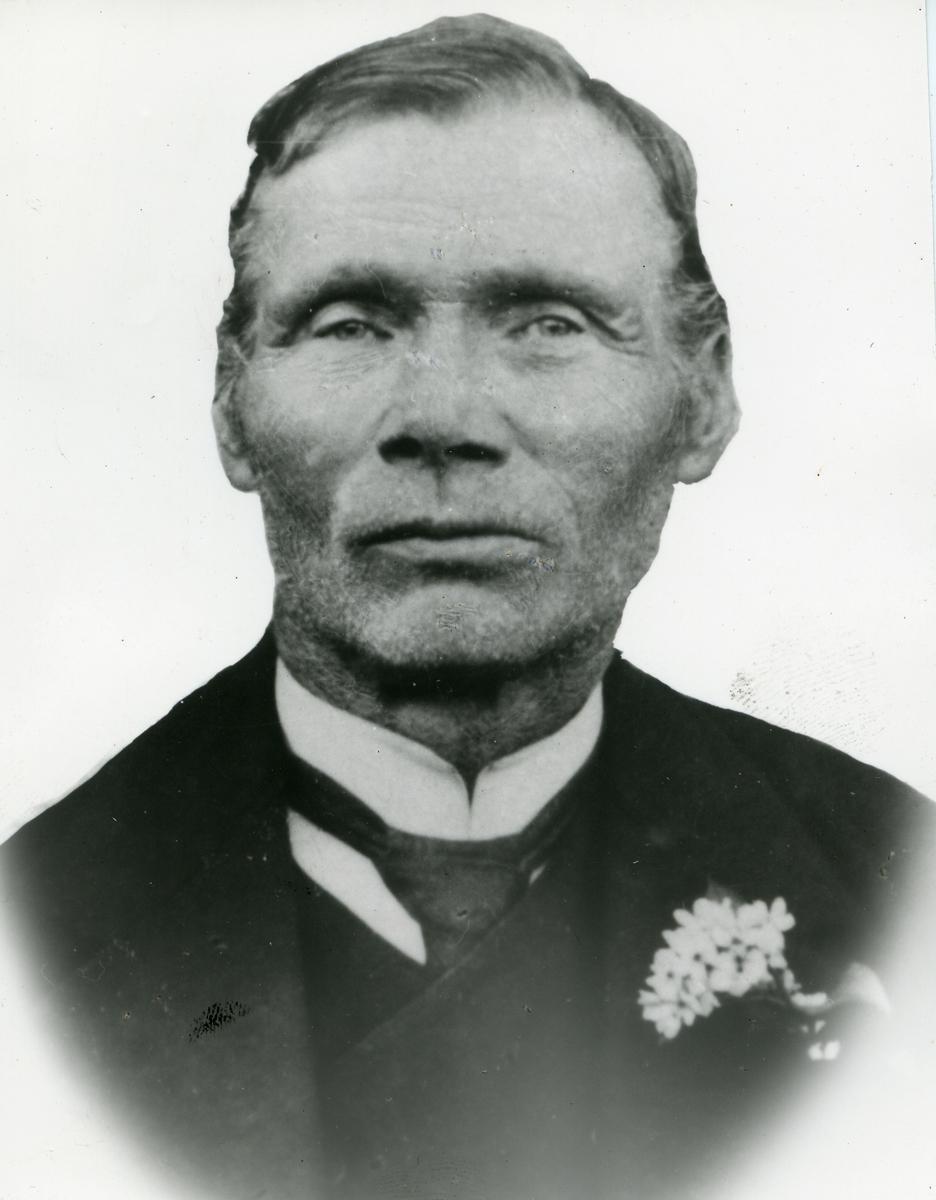 Portrett av Torger Vidste. Han har blomsterpynt på jakkeslaget og slips og skjorte.
