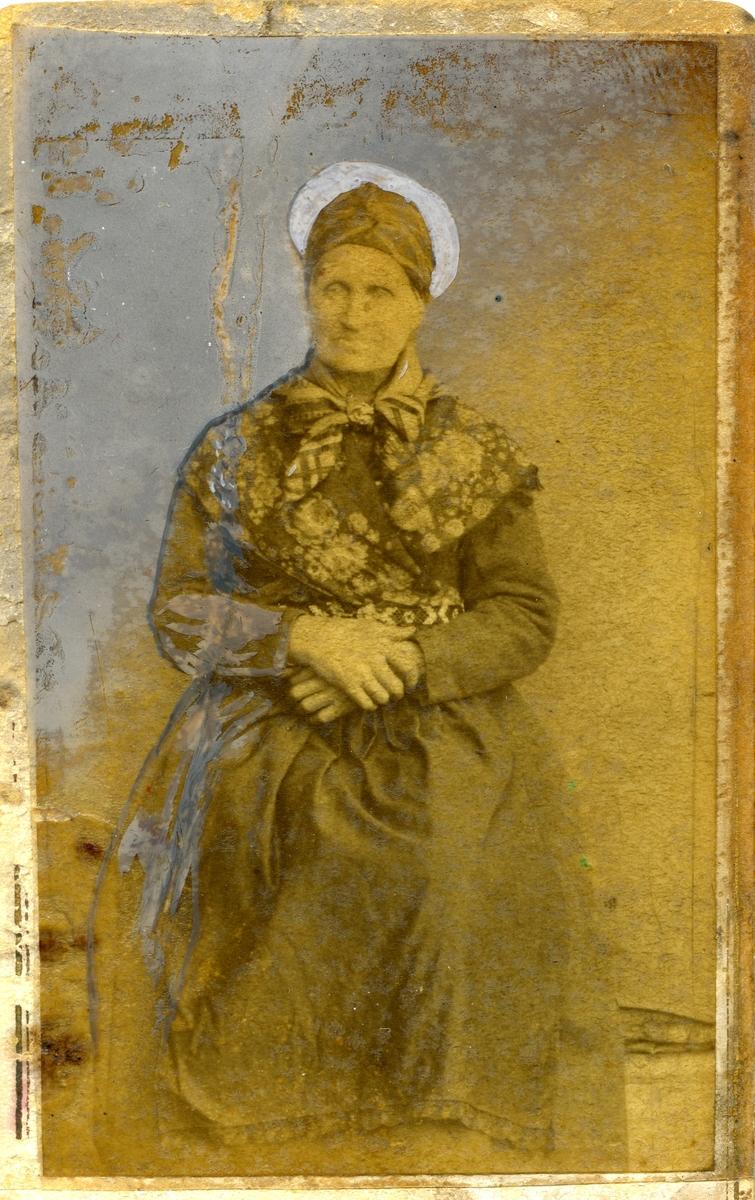 Portrett i helfigur av kvinne kledd i Bunad/folkedrakt. Hun har et sjal over skuldrene og silketørkle i halsen. Berlebelte og rull på hodet.