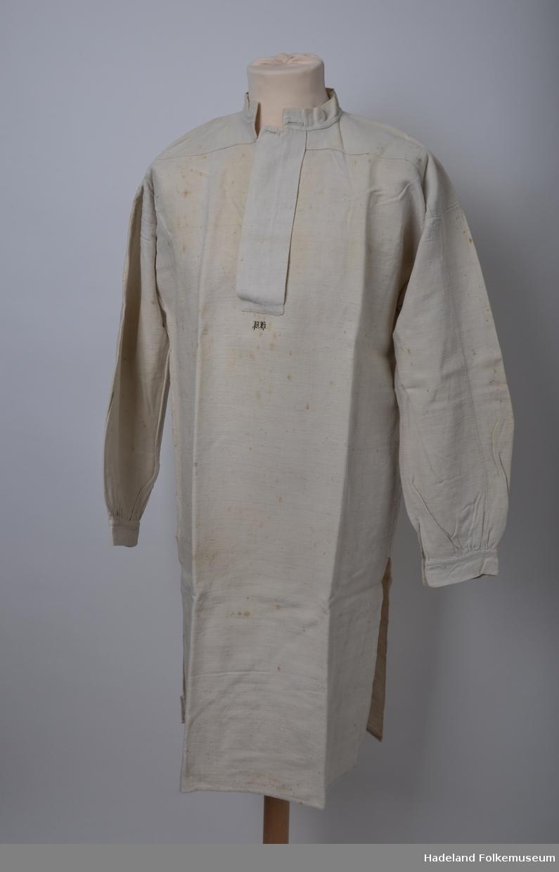 Mannsskjorte.  Hvitt kypertvevet bomullsstoff med bomullsrenning og lin islett. Håndvevd. Primærsnitt med halssplitt med stolpe med knapphull øverst. Linning med knapphull. Skulderstykke. Ermer med kile under rynket til ermlinning med knapphull. Splitt nederst i sidene.