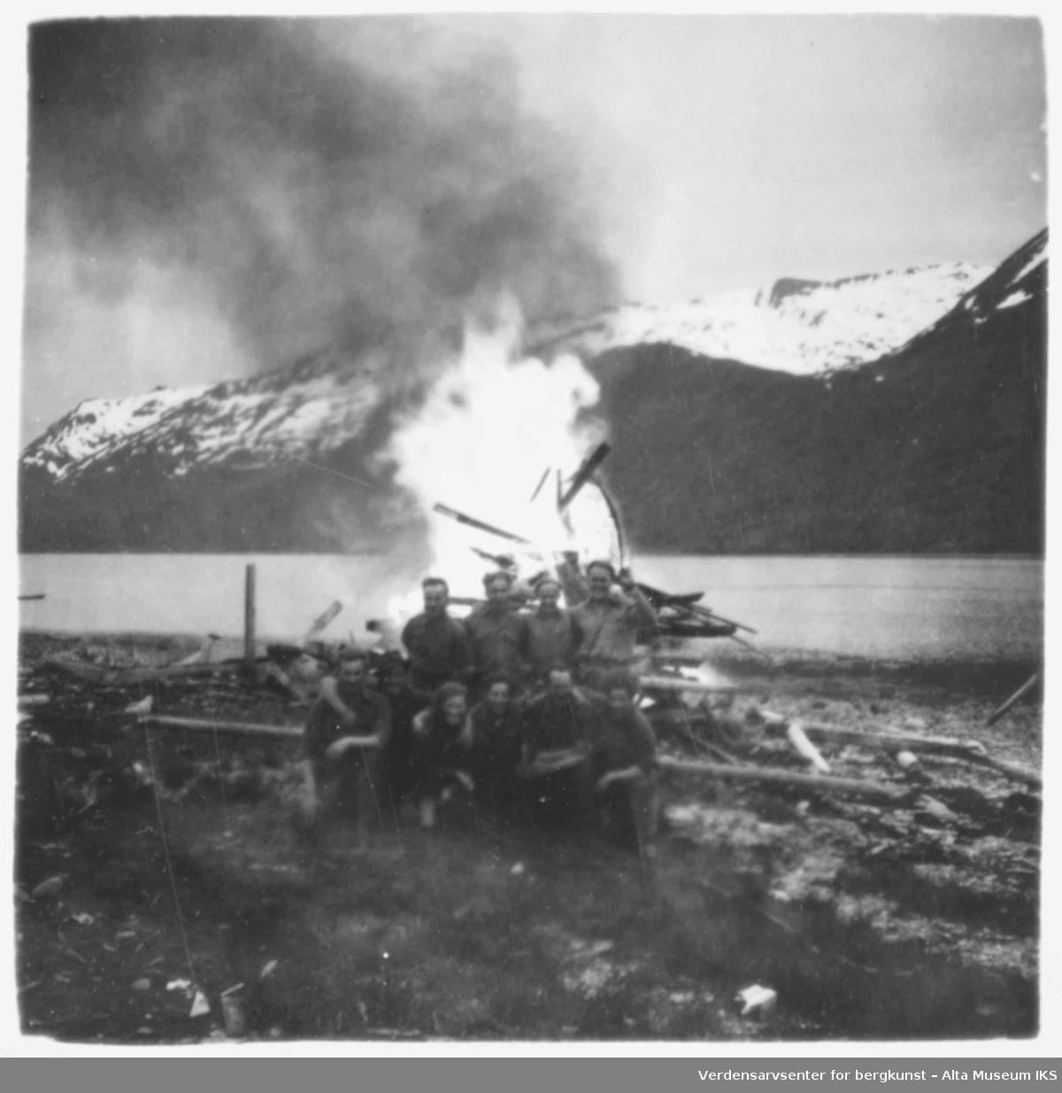 Soldater poserer foran et bål, ved en fjord.